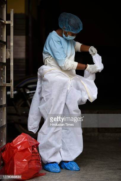 A health worker removes her PPE kit after the end of coronavirus sample collection drive at Shiv Nagar near Teen Murti on August 14 2020 in Gurugram...