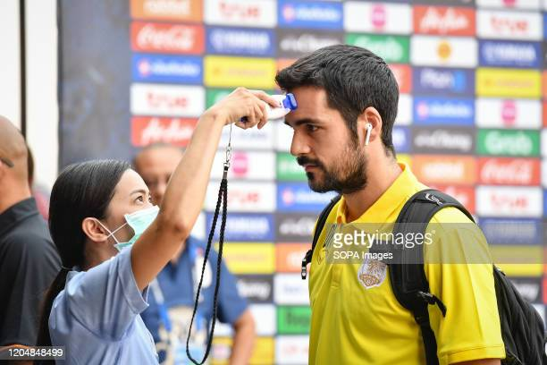 Health worker screens the temperature of a footballer before the Thai League 2020 match between Buriram United and Port FC at Buriram Stadium to...