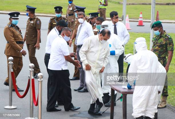A health worker sprays disinfectant of Sri Lanka's former speaker of the Parliament Karu Jayasuriya as he arrives to attend the funeral of Ceylon...