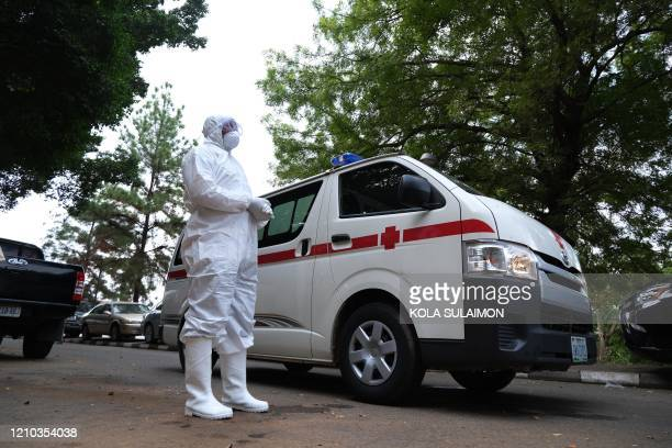 Health worker stands next to an ambulance carrying the body of Nigerias Chief of Staff , Abba Kyari, in Abuja on April 18, 2020. - Abba Kyari, the...