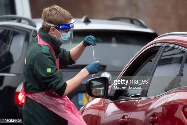Health worker takes a swab from a person in a car at Ashton Gate Stadium on January 11, 2021 in Bristol, England. The location is one of several mass...