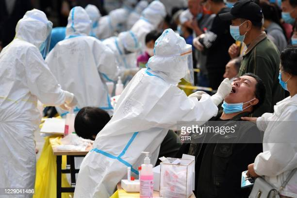 Health worker takes a swab from a resident to be tested for the COVID-19 coronavirus as part of a mass testing program following a new outbreak of...