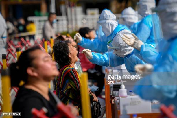 Health worker takes a swab from a resident to be tested for the COVID-19 coronavirus in Qingdao, in China's eastern Shandong province on October 12,...