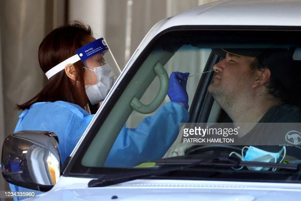 Health worker takes a swab sample of a resident at a Covid-19 drive-through testing clinic in eastern Brisbane on July 31 as Australia's...