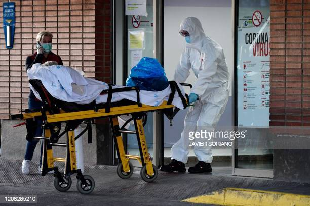 Health worker transfers a patient on a stretcher at the Severo Ochoa hospital in Leganes, on March 26, 2020. - Spain's coronavirus toll surged above...