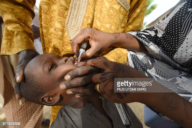 Health worker tries to immunise a child during a vaccination campaign against polio at HotoroKudu Nassarawa district of Kano in northwest Nigeria on...