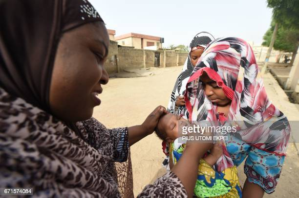 Health worker tries to immunise a child during vaccination campaign against polio at HotoroKudu Nassarawa district of Kano in northwest Nigeria on...