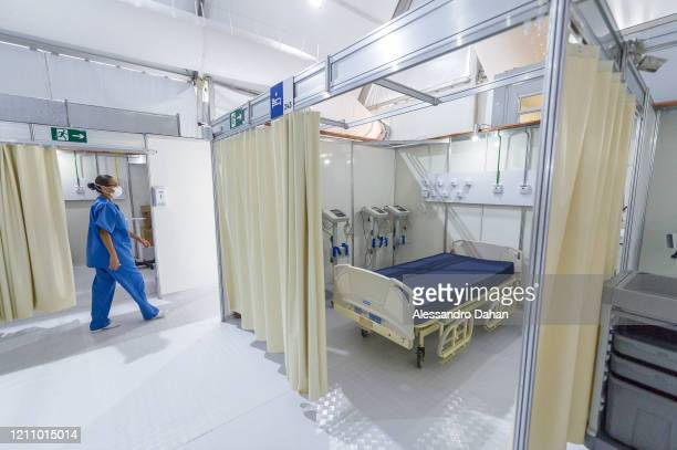 A health worker walks by the LagoaBarra field hospital on April 25 2020 in Rio de Janeiro Brazil The hospital has 7 thousand square meters with a...