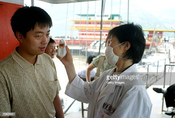 Health worker wearing a face mask to protect against the Severe Acute Respiratory Syndrome virus checks the temperature of a traveler boarding a boat...