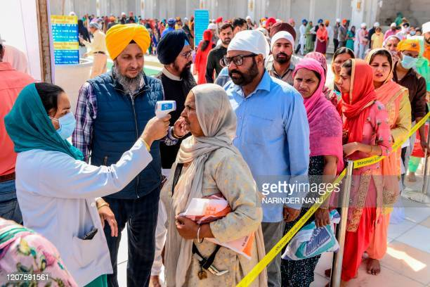 Health worker wearing a facemask checks the body temperature of devotees amid concerns over the spread of the COVID-19 novel coronavirus, at the...