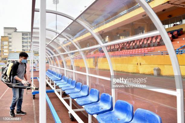 A health worker wearing a facemask sprays disinfectant on the team dugout amid concerns of the spread of the COVID19 novel coronavirus at the Hang...