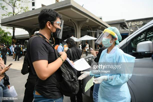Health worker wearing a personal protective equipment suite assisting a man in a queue for verification of his documents during a swab test drive...