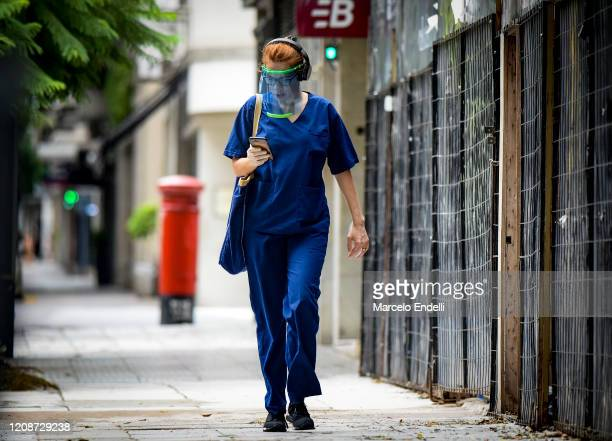 A health worker wearing a protective plastic mask looks at her cell phone on March 31 2020 in Buenos Aires Argentina Last Sunday President Fernandez...