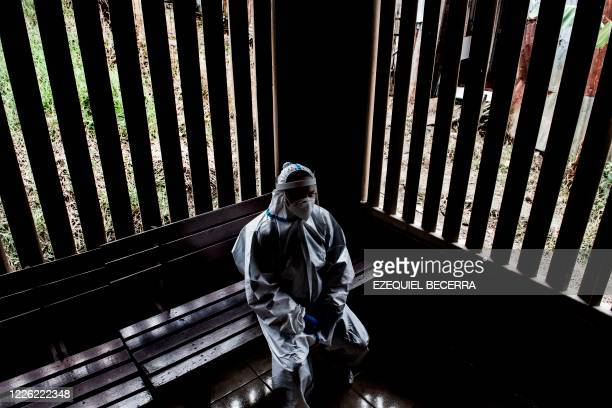 A health worker wearing a protective suit against the spread of the novel coronavirus COVID19 rests at a health centre in a lowincome neighbourhood...