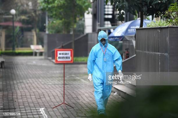 Health worker wearing a protective suit and face mask amid concerns of the spread of the COVID-19 coronavirus walks inside a quarantine area in Thanh...