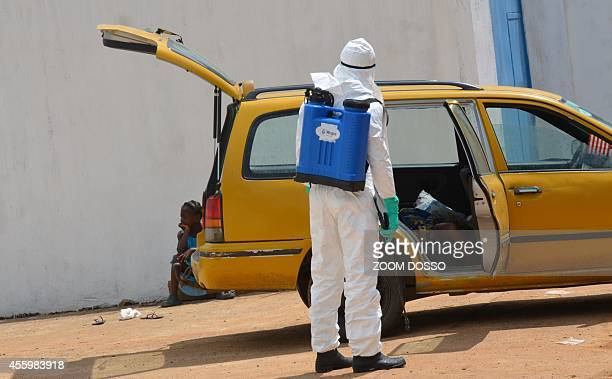 A health worker wearing a protective suit disinfects a taxi on September 23 2014 outside the Island Clinic a new Ebola treatment centre that opened...