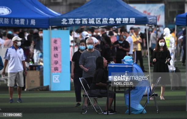Health worker wearing a protective suit takes a swab test from a woman at Guangan Sport Center for people who visited or live near the Xinfadi Market...