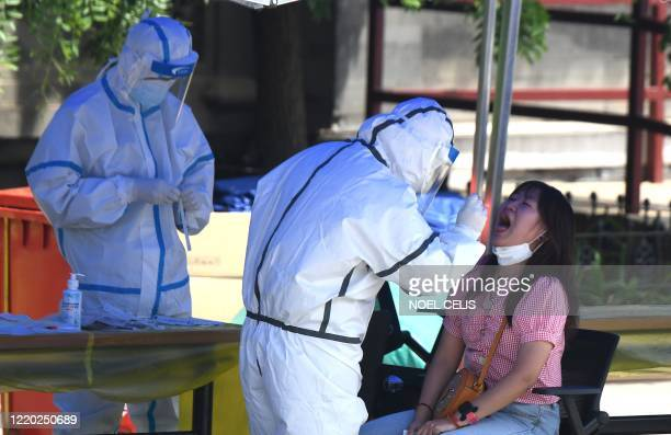 A health worker wearing a protective suit takes a swab test on a woman for those who are living or visited the Xinfadi Market in Beijing on June 16...