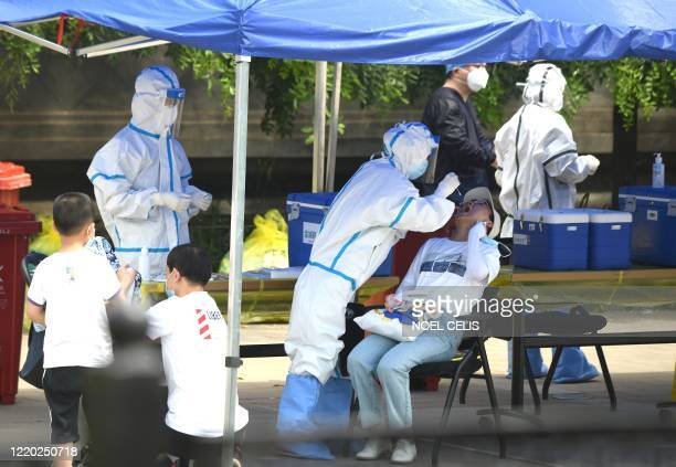 Health worker wearing a protective suit takes a swab test on a woman in Beijing on June 16, 2020. - China reported another 27 domestically...