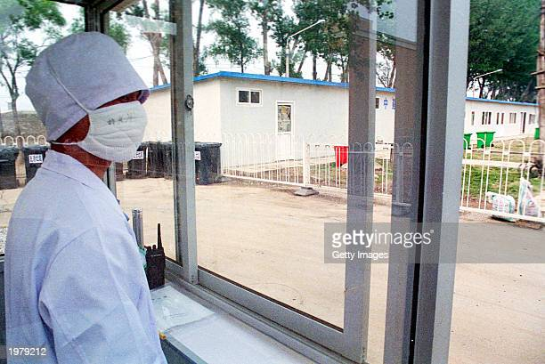 A health worker wearing a surgical mask watches the access to the restricted section of the newly built 1000 bed SARS hospital in Xiaotangshan...