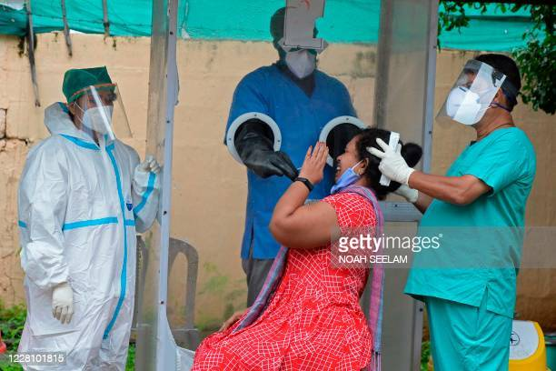 Health worker wearing personal protective equipment gear collects a swab sample from a woman at a free COVID-19 coronavirus testing centre in...