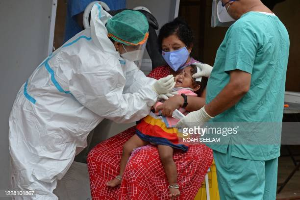Health worker wearing personal protective equipment gear collects a swab sample from a child at a free COVID-19 coronavirus testing centre in...