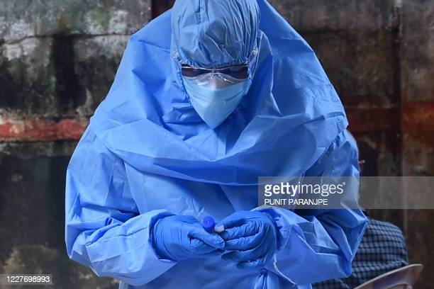Health worker wearing Personal Protective Equipment gear holds a swab sample of a resident during medical screening for the COVID-19 coronavirus, at...