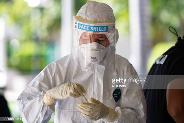 Health worker wearing personal protective equipment handles completed Covid-19 nasal swab tests at Ministry of Public Health on November 9, 2020 in...