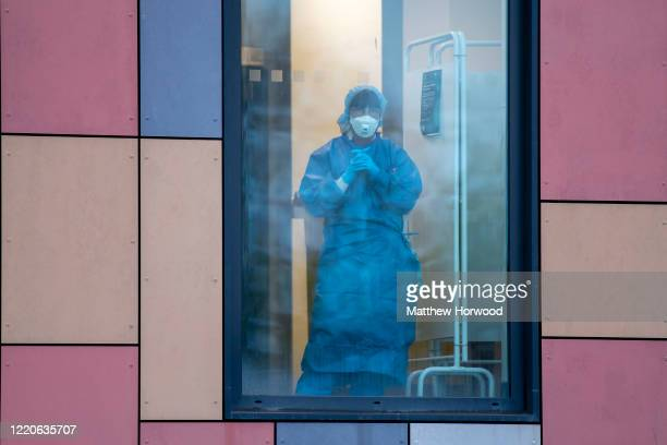 A health worker wearing PPE looks on from a window at the Royal Gwent Hospital on April 23 2020 in Newport United Kingdom Following the success of...