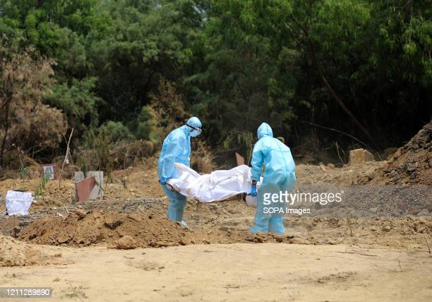 Health worker wearing protective gear as a precaution carry the body of a Central Reserve Police Force personnel who died of the coronavirus disease...
