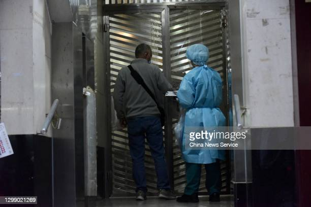 Health worker wearing protective suit transfers a resident living at Tung Fat Building in North Point on January 27, 2021 in Hong Kong, China.