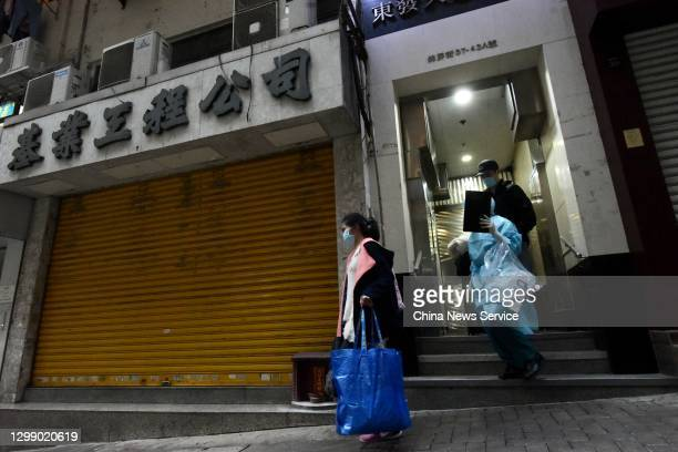 Health worker wearing protective suit transfers residents living at Tung Fat Building in North Point on January 27, 2021 in Hong Kong, China.