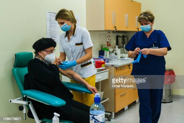 Health worker wears a protective face mask and gloves as she gives a Pfizer/BioNTech COVID-19 jab to an elderly woman at the Krakow University...