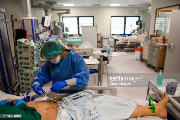 Health worker wears a protective suit, face mask and gloves as she performs an electrocardiogram on a COVID-19 patient at the ICU of Krakow...