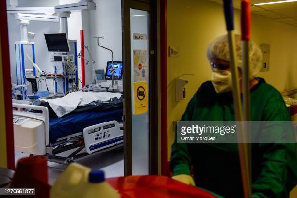 Health worker wears a protective suit, face mask and gloves as she passes by a black bag with a COVID-19 diseased patient body at the ICU of Krakow...