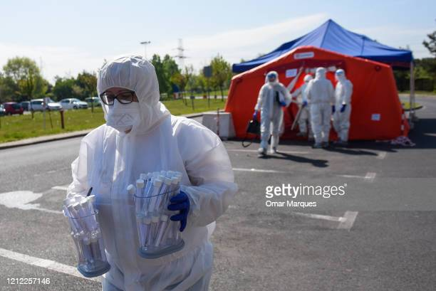 A health worker wears a protective suit gloves mask and a face shield as she carries saliva samples from miners to test for COVID19 at Rybnik...