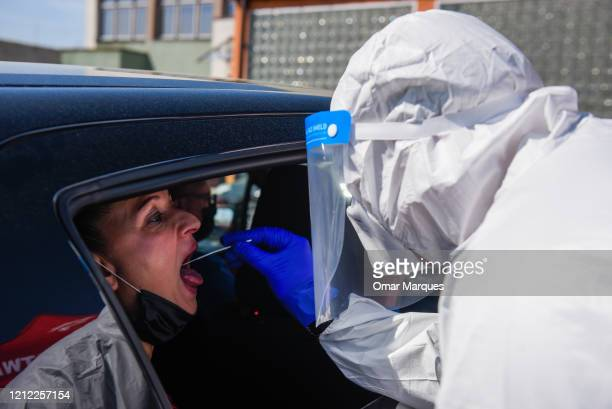 A health worker wears a protective suit gloves mask and a face shield as she takes a saliva sample from a miner relative to test for COVID19 at...