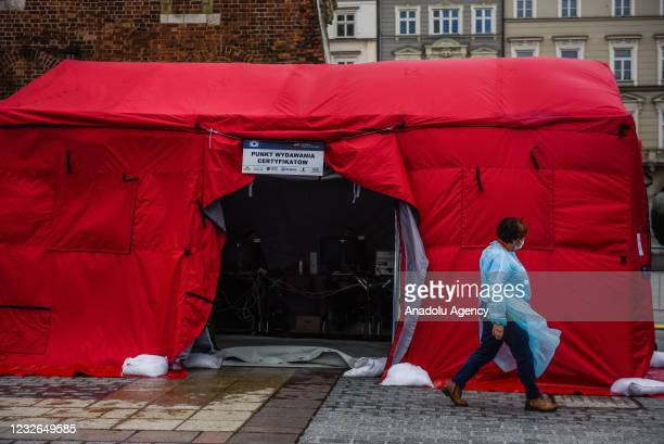 Health worker wears protective equipment as she walks inside the mobile vaccination point at Krakow's UNESCO listed Main Square on May 02, 2021 in...