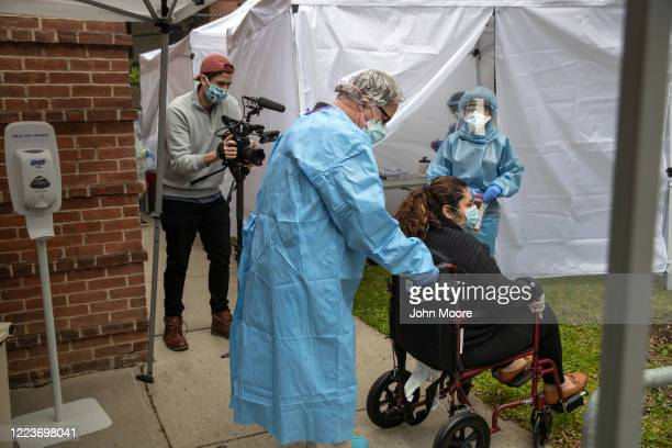 A health worker wheels Guatemalan immigrant Zully away after she was tested for COVID19 on May 8 2020 in Greenwich Connecticut Zully was retested at...
