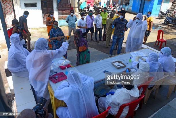 Health workers and doctors conduct thermal screening and pulse test of a resident at Dharavi during Covid-19 pandemic, on June 29, 2020 in Mumbai,...