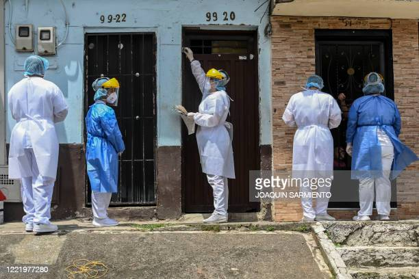 Health workers are pictured during a random testing at the Santa Cruz neighborhood in Medellin Colombia on June 14 2020 during the Covid19...