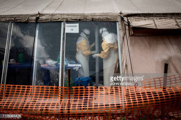 TOPSHOT Health workers are seen inside the 'red zone' of an Ebola treatment centre which was attacked in the early hours of the morning on March 9...