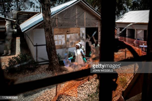 TOPSHOT Health workers are seen through a bullet hole left in the window of an Ebola treatment centre which was attacked in the early hours of the...