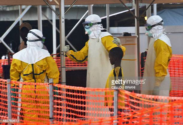 Health workers are seen with a young patient under quarantine at the Nongo ebola treatment centre in Conakry Guinea on August 21 2015 The World...
