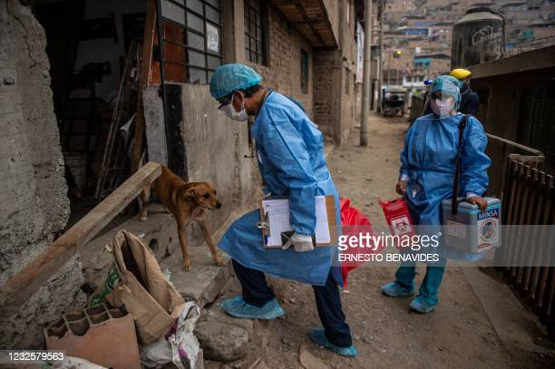 Health workers arrive to inoculate elderly citizens with doses of the Pfizer-BioNTech vaccine against COVID-19, at their house at El Agustino...