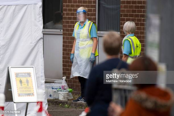Health workers at a temporary coronavirus testing centre at the Oldway House Car Park on September 10, 2020 in Porth, Wales. A temporary walk-in...