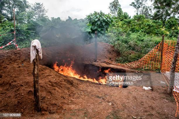 Health workers burn mattresses used by patients with Ebola virus on August 21 2018 in Mangina near Beni in the North Kivu province Sixtyone people...