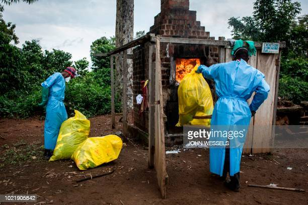 Health workers burn medical waste generated during care of patients with Ebola virus on August 21 2018 in Mangina near Beni in the North Kivu...