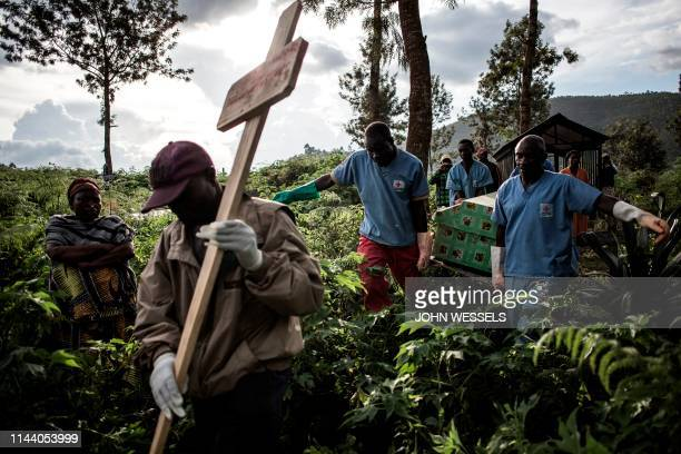 TOPSHOT Health workers carry a coffin containing a victim of Ebola virus on May 16 2019 in Butembo The city of Butembo is at the epicentre of the...