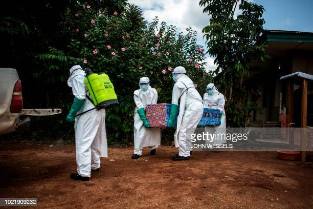 Health workers carry out the body of a patient with unconfirmed Ebola virus on August 22 2018 in Mangina near Beni in the North Kivu province...
